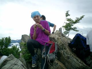 山頂の岩に腰掛休む仲間